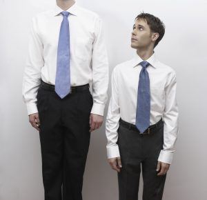Short business man standing next to tall man